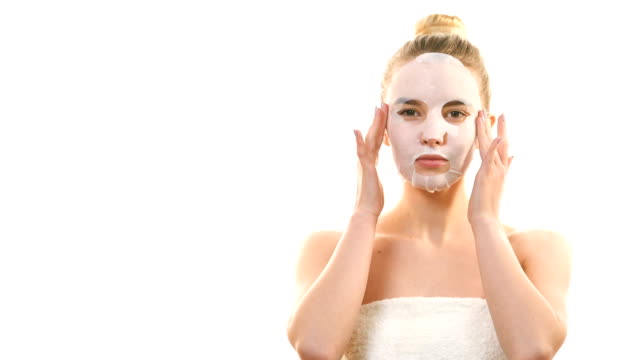 the cute girl with a clean mask touching the face on the white background - spa facial stock videos & royalty-free footage