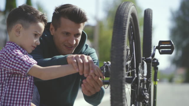 The dad teaching his son to fix the bicycle. slow motion