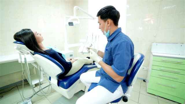 The dentist closer to patient sitting in the dental chair and speaks to her, smiling video