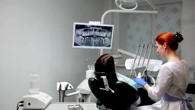 The dentist completes his work with a patient. Removes Bor machine and gives a girl a mirror to assess the work. The girl looks at your teeth and thanked the dentist video