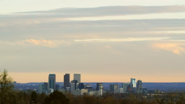 The Denver City Skyline at Sunset Under a Cloudy Sky with the Rocky Mountains in the Background