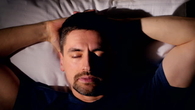 The depressed man in bed. Close-up. 4K. The portrait of the man waking up. Close-up. double bed stock videos & royalty-free footage
