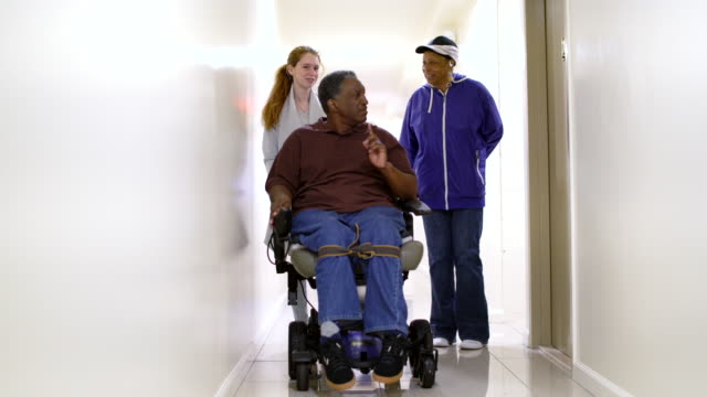 The disabled African-American man in wheelchair, accompanied with Black woman and White teenager girl, in the corridor of the residential living building in Bronx video