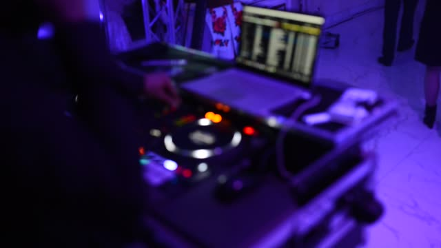 the dj at the disco is working behind the remote control. dance floor and light music. - telecomando background video stock e b–roll
