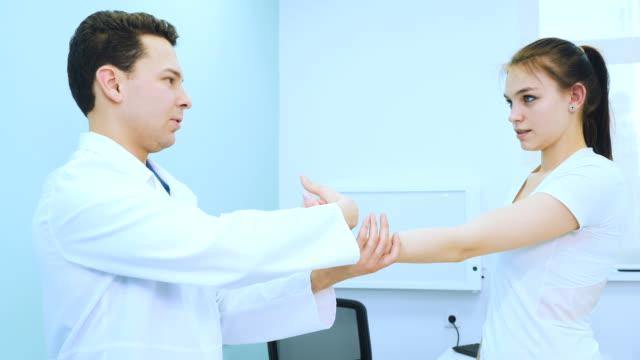 the doctor examines the hand of the girl in hospital - giuntura umana video stock e b–roll