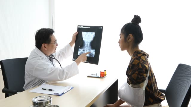 The doctor is explaining about the brain X-ray results to a female patient in his office at Hospitals.(4k resolution)