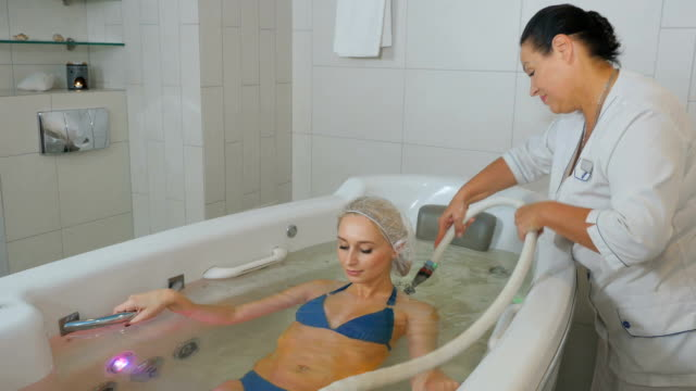 the doctor making the hedromassage of the back of the woman in bathtube - china drug video stock e b–roll