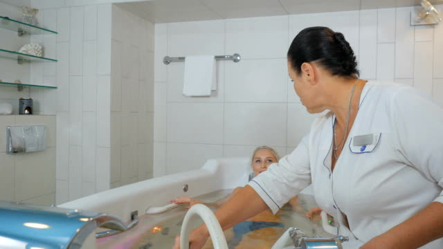 the doctor massages the pretty woman in hydrobath - china drug video stock e b–roll