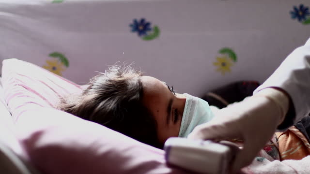 vídeos de stock e filmes b-roll de the doctor measures the patient's fever - doença