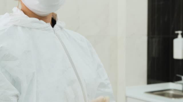 läkaren bär en vit skyddsdräkt på kliniken och zippar upp klänningen - aftonklänning bildbanksvideor och videomaterial från bakom kulisserna