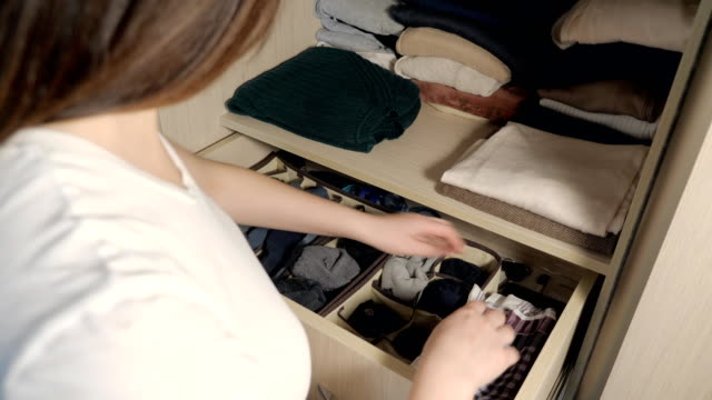 The drawer with underwear in the closet. Housewife organizing clothes in wardrobe, close up. The drawer with underwear in the closet, slow motion. Housewife organizing clothes in wardrobe, close up. order stock videos & royalty-free footage