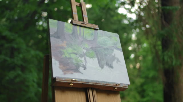 The drawing stands on an easel in the middle of the meadow in a green park