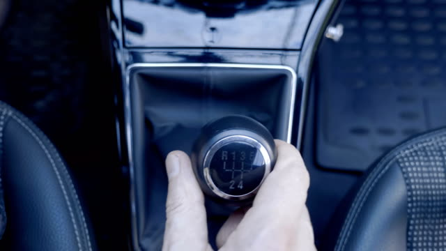 the driver's hand takes a lever and engages the gears in the transmission - dźwignia zmiany biegów filmów i materiałów b-roll