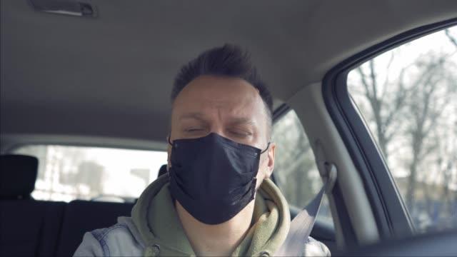 stockvideo's en b-roll-footage met de drijvende automan die beschermingsmasker op het gezicht draagt dat in de auto in beschikbare handschoenen tijdens de pandemie van het coronavirus zit. prores 422 - mirror mask