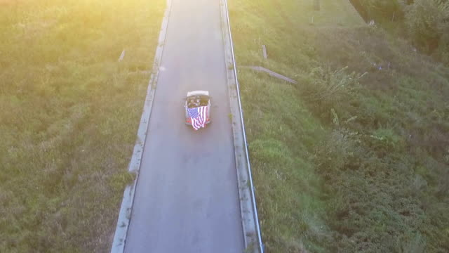 The drone flies over the cabriolet car with a large us flag. Children are waving to the drone. video