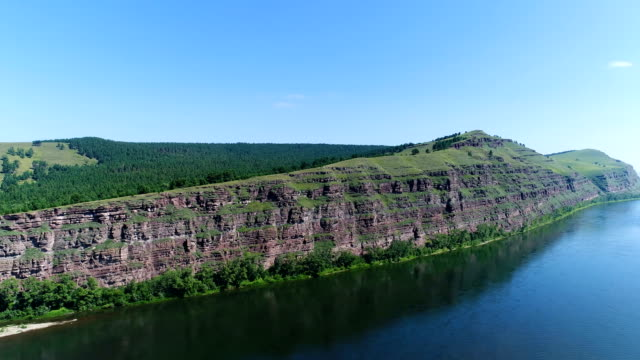 The drone flies over the river near the rock. video
