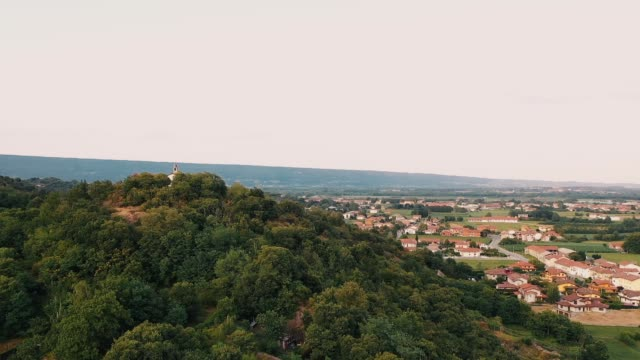 The drone rises above the horizon. There is an Italian village landscape