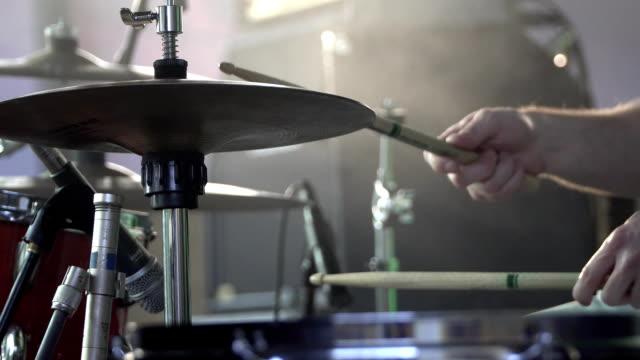 trummisen spelar trumset på konsert närbild av plattor för rytm. rockkonsert - akustisk gitarr bildbanksvideor och videomaterial från bakom kulisserna