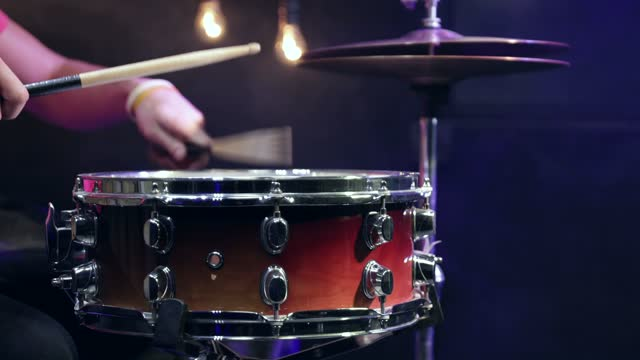 The drummer plays the snare drum with sticks close up.