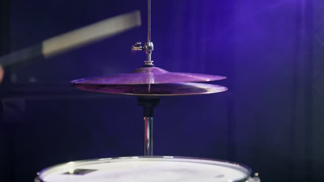 The drummer plays with sticks on the hi-hat close-up in the dark with smoke.