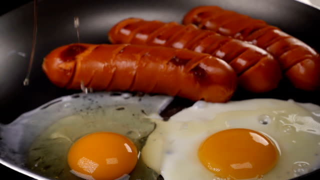 The egg falls on a hot frying pan with sausages video