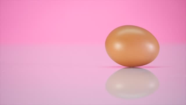 The egg spins on a table on a pink background video