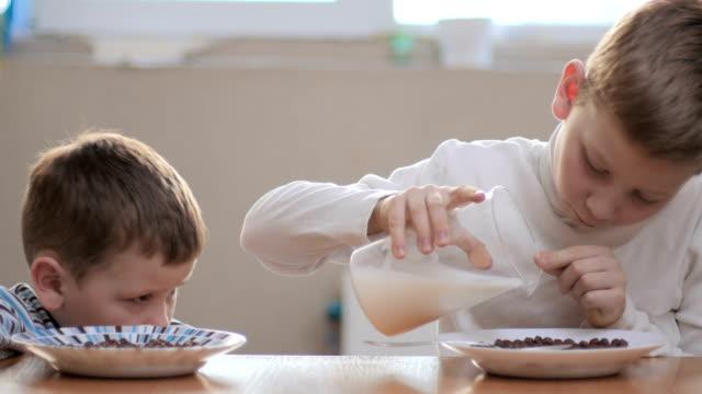 den äldsta pojken lägger mjölk till plattan - tallrik uppätet bildbanksvideor och videomaterial från bakom kulisserna