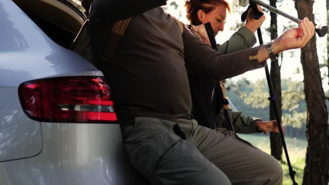 老夫婦は山に到着したばかりで、ハイキングの準備をしています。彼らは車のトランクに座ってポールを調整し、背中にバックパックを持っています - disruptagingcollection点の映像素材/bロール