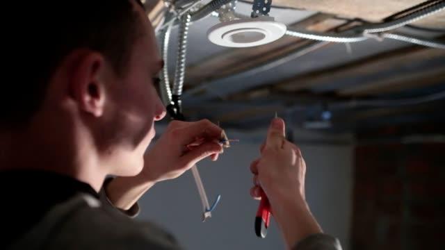 vídeos de stock, filmes e b-roll de o eletricista limpa o fio elétrico da isolação. - eletricista