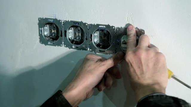 die elektriker behebt das tv-kabel in der wand. - schraube stock-videos und b-roll-filmmaterial