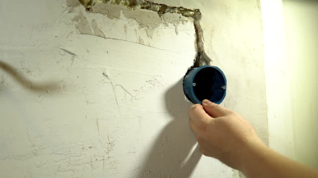 The electrician installs a round mounting box in the hole in the wall video