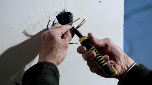 vídeos de stock, filmes e b-roll de o eletricista instala o interruptor da luz. - eletricista