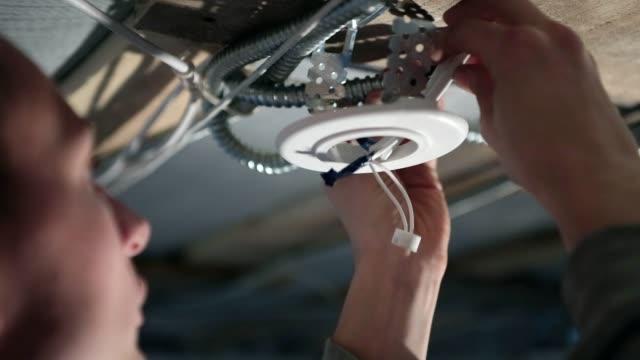 El electricista prepara los cables para la instalación de una lámpara de techo - vídeo
