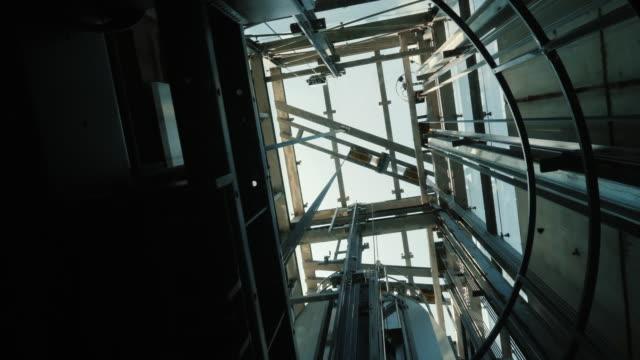 hissen går ned i axeln. på toppen, kan du se mekanismen av hissen, kablar och den blå himlen - construction workwear floor bildbanksvideor och videomaterial från bakom kulisserna