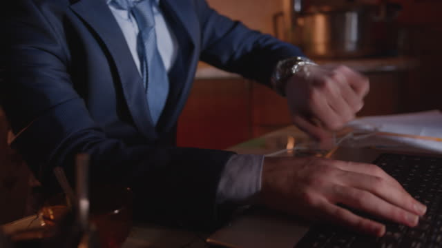 the employee or blogger in a suit looks at his wristwatch while he is writing or financing with a laptop and goes on. - {{relatedsearchurl(carousel.phrase)}} video stock e b–roll