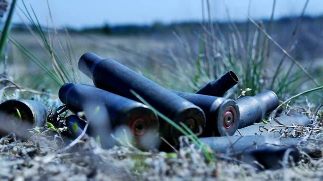The empty machine gun shells in the grass video