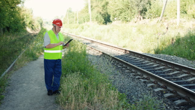 The engineer fixing data on the tablet when checking serviceability of railroad video
