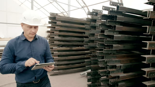The engineer keeps a record in the warehouse of metal structures video