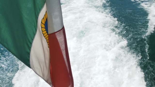 The Ensign Flag of Italy Above the Trail of a Motorboat in the Waters of Lake Garda video