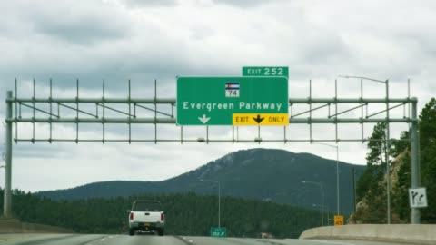 """vidéos et rushes de le """"exit 252: evergreen parkway (colorado highway 74)"""" sortie signe du point de vue d'un véhicule conduite westbound sur l'interstate 70 dans les montagnes rocheuses du colorado sur une journée partiellement nuageux - autoroute"""
