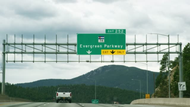 """der """"exit 252: evergreen parkway (colorado highway 74)"""" exit sign from a vehicle es perspective driving westbound on interstate 70 in the rocky mountains of colorado an einem partly cloudy day - schild stock-videos und b-roll-filmmaterial"""