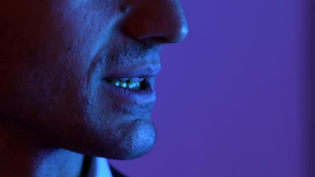 vidéos et rushes de le visage d'un homme parlant sur le fond bleu - bouche