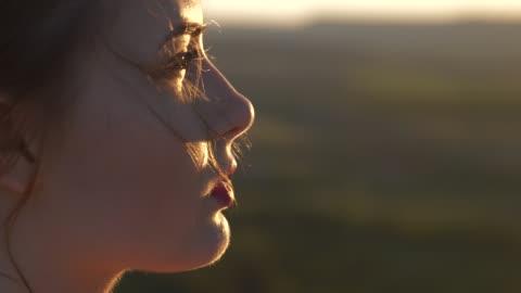 vídeos y material grabado en eventos de stock de el rostro de una joven hermosa que mira el sol, el viento mueve su pelo - sol