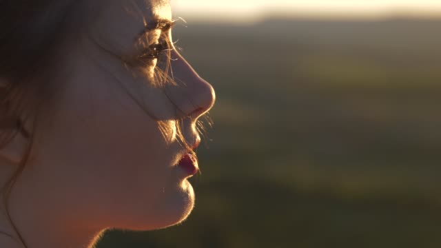 The face of a young beautiful woman who looks at the setting sun The wind shakes her hair video