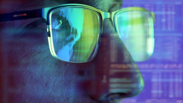 the face of the man in glasses looking on the display on the hologram background - odbicie zjawisko świetlne filmów i materiałów b-roll