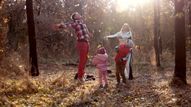 The family has fun in autumn park and throw leaves up video
