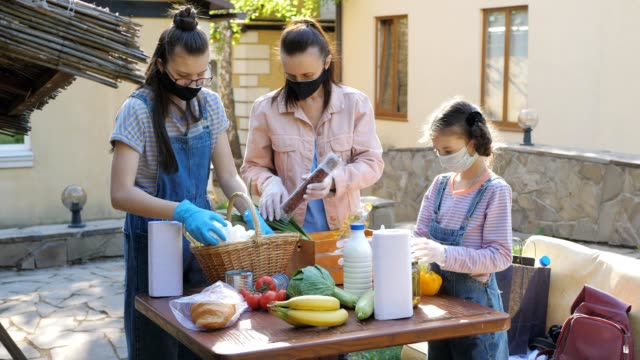 The family is engaged in charity work. A woman with her daughters in the courtyard of the house put food in a basket to help low-income people.