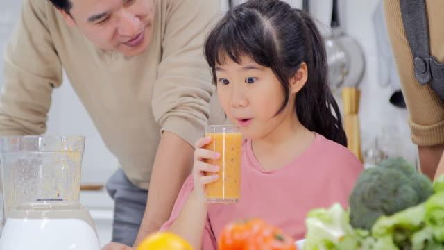 家族は、一緒に父と女の子のキッチンで飲み物果物に満足です。タイ人家族の家庭で - 母娘 笑顔 日本人点の映像素材/bロール