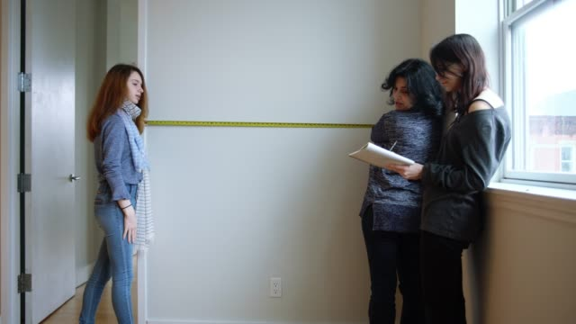 The family, the mother, and two teenager daughters measures the empty room in the new apartment to planning furniture placement. The family, the mother, and two teenager daughters measure the empty room in the new apartment to planning furniture placement. Brooklyn, New York City, USA. 4K UHD video footage. measuring stock videos & royalty-free footage