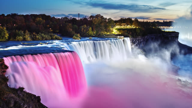 the famous niagara falls in the evening. spotlights illuminate the waterfall is beautiful white and pink light - niagara falls stock videos & royalty-free footage